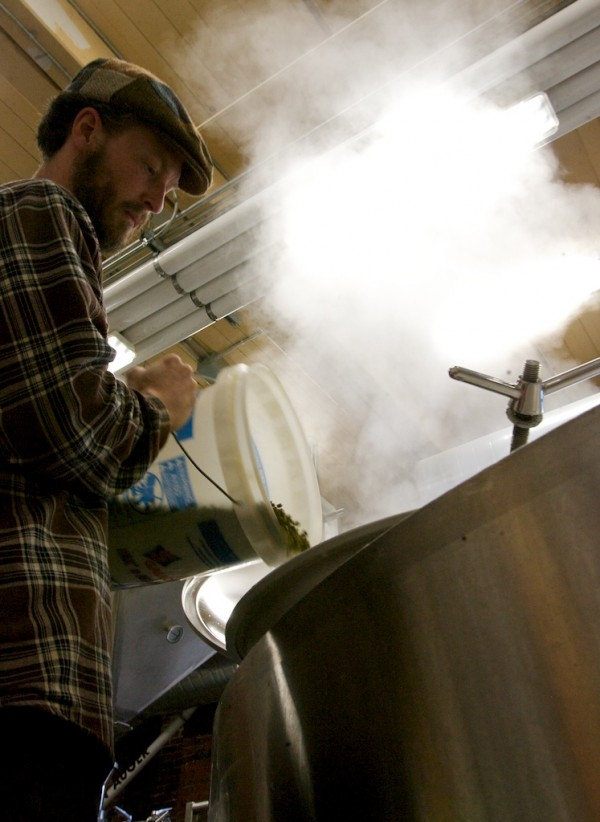 BREWER GEOFF NEWMAN adds buckets of hop pellets to a steaming batch of Stowaway IPA beer, after boiling, for aroma at Baxter Brewing in Lewiston.