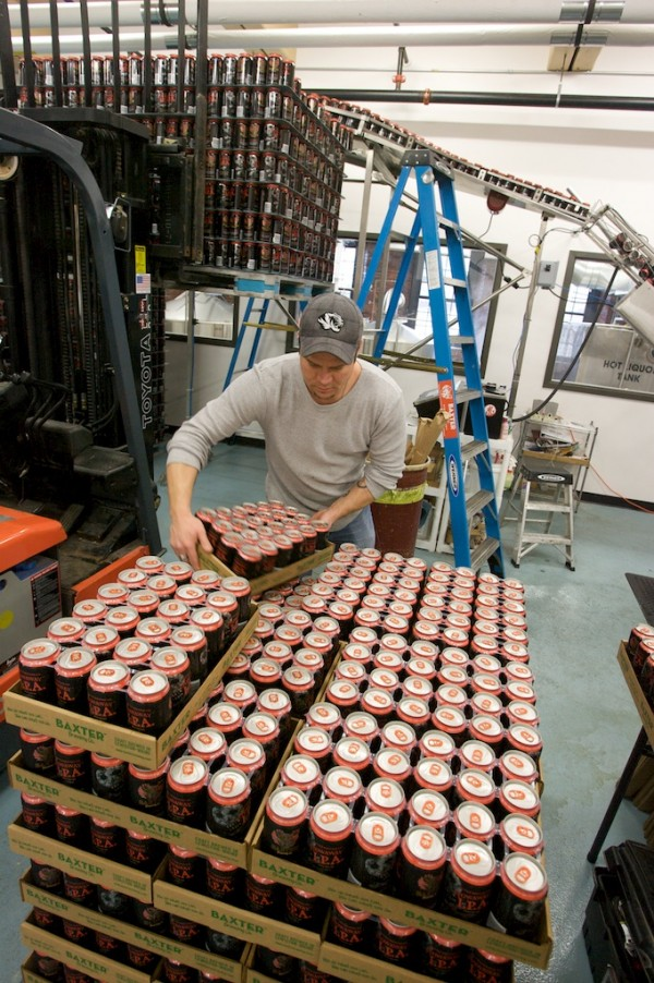 JON GREEN stacks racks of Baxter Brewing's Stowaway IPA as it comes off the canning line at the brewery in Lewiston.
