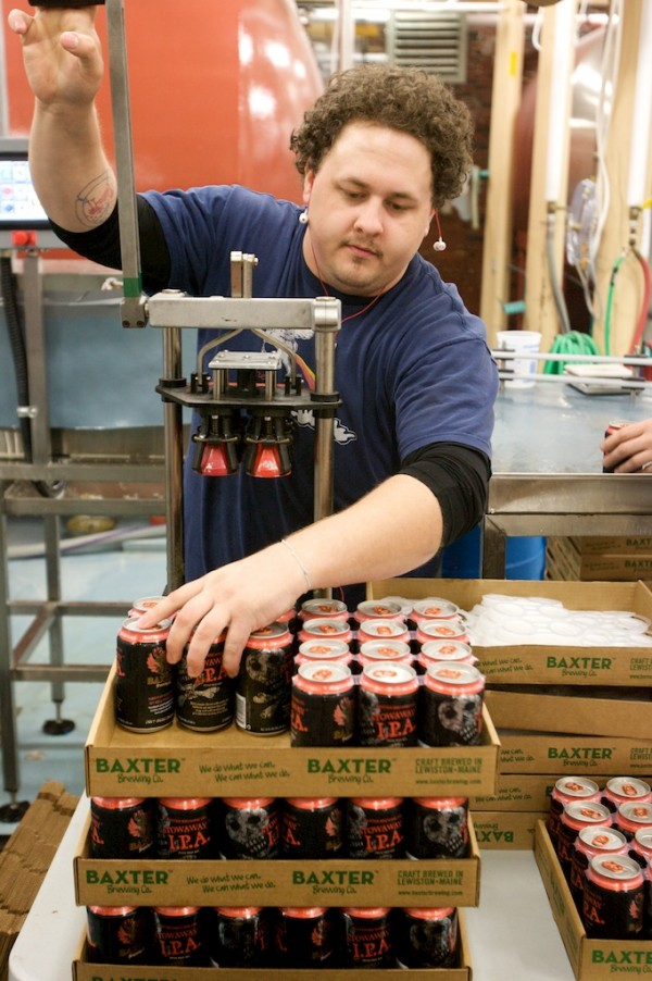 JASON HARRIS bundles cans of beer into six packs at the Baxter Brewery in Lewiston. All three of Baxter's beers are sold either on draft or in cans, not bottles. The reasoning is threefold: cans are easier to recycle, cans keep beer fresher, longer, and cans can't break like glass.
