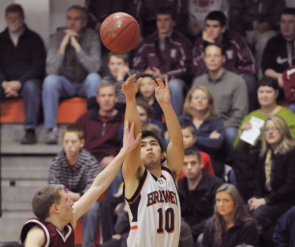 Brewer boy's basketball team player Yuhi Sasaki (10) puts up a three-point shot attempt over Bangor defender Johnn Szewczyk in the first half of their game in Brewer Thursday, Dec. 22, 2011.