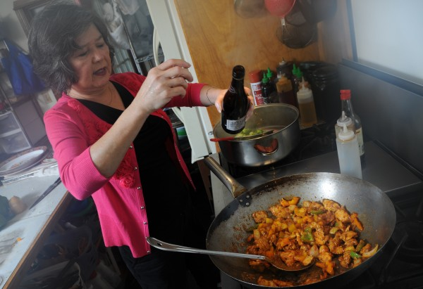 Bich Nga Burrill adds a little cooking wine to her &quotMy Diet Chicken&quot as she cooks it in her home based kitchen in Winterport on Thursday, Dec.15, 2011. Burrill has published her second cookbook, featuring Vietnamese recipes.