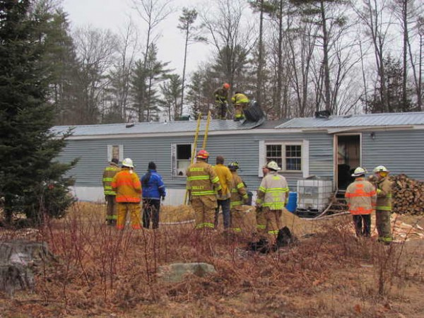 Firefighters cut into the roof of a mobile home on Riverbend Road in Buckfield on Wednesday, Dec. 21 after a fire erupted. A woman and a dog escaped unharmed.