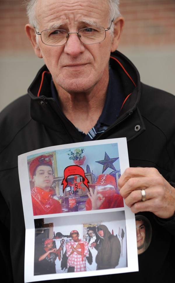Alan Suddy, grandfather to murder victim  John &quotBobby&quot Surles, displays two pictures outside the Penobscot County Judicial Center in Bangor on Friday, Dec. 2, 2011, that he says depict Zachary Carr and other Bangor area youth posing in gang colors and flashing gang signs.