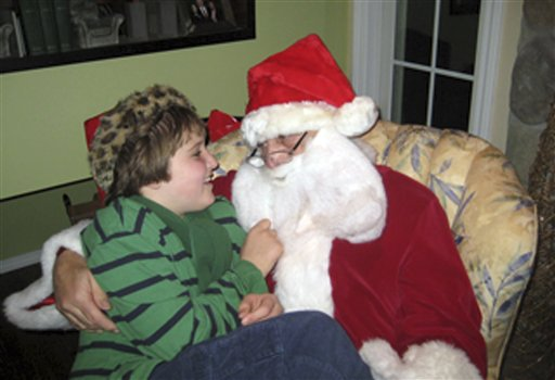 "This Dec. 11, 2011 photo provided by Darlene Borre, shows her son, Ben Borre, 10, of West Hartford, Conn., with an autism-friendly Santa Claus, Ray Lepak of Manchester, Conn., who is also  Ben's grandfather. For families of many children on the autism spectrum, a visit with Santa Claus at Christmas can be nearly impossible, unless they''re visiting one of the growing number of ""sensitive"" Santas."