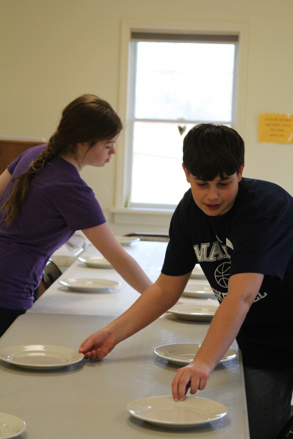 Kyle Waters, 13, an eighth-grader at St. George School, helped set up plates for a monthly lunch for seniors. The eighth-graders donate their time to various community projects as part of their school time.