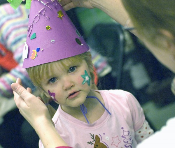 Three-and-a-half-year-old Sophia gets a helping hand on the pitch of her party hat as part of New Year's Eve festivities at the Maine Discovery Museum.