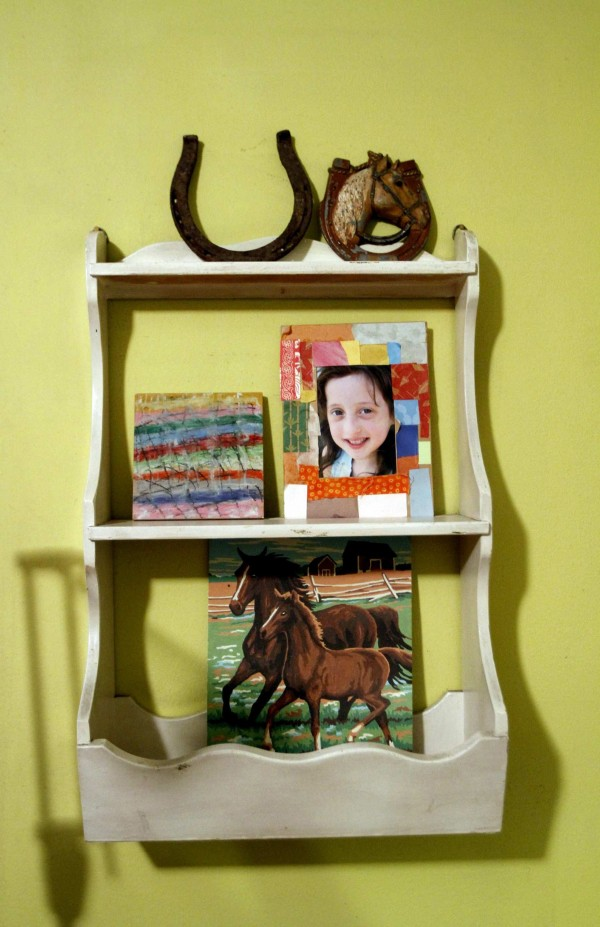 Illustrator Emily Green has created a brand of housewares devoted to kids. Here, a craft shelf displays paintings.