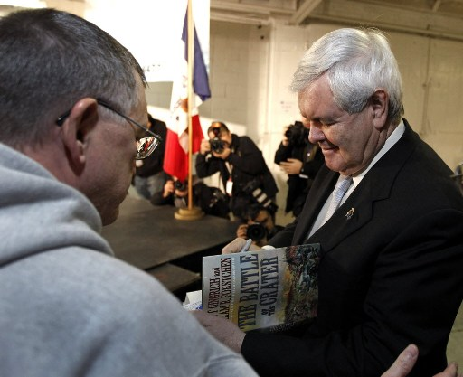 Republican presidential candidate former House Speaker Newt Gingrich autographs a book before a campaign stop at Global Security Services in Davenport, Iowa, Monday, Dec. 19, 2011.