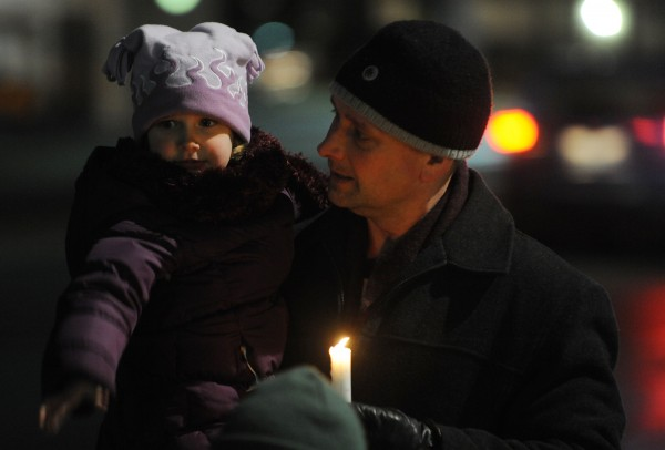 Darryl Lyon and his daughter Marin, along with other family members not pictured, walk along Main Street in Bangor on Thursday, Dec. 22, 2011, as part of The Longest Night, Bangor's annual homeless candlelight vigil and remembrance.
