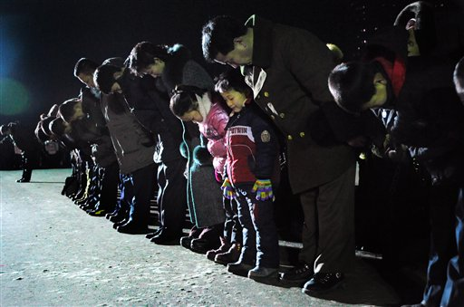 Mourners bow before a portrait of the late leader Kim Jong Il, hanging outside the Pyongyang Circus Theater in Pyongyang, North Korea on Saturday, Dec. 24, 2011.