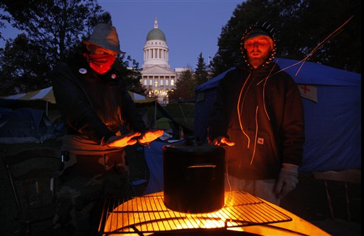Occupy Augusta protesters warm their hands while brewing coffee on a fire pit at their encampment across from the State House in Augusta, Maine, Oct. 28, 2011.