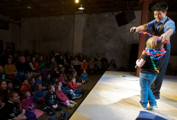 Magician Norman Ng pulls a long crepe paper chain from a tiny hat  in Acorn Productions' annual Christmas week festival of physical comedy, Phyzgig, at Space Gallery in Portland on Tuesday. The festival features a dozen shows running through the end of the week.