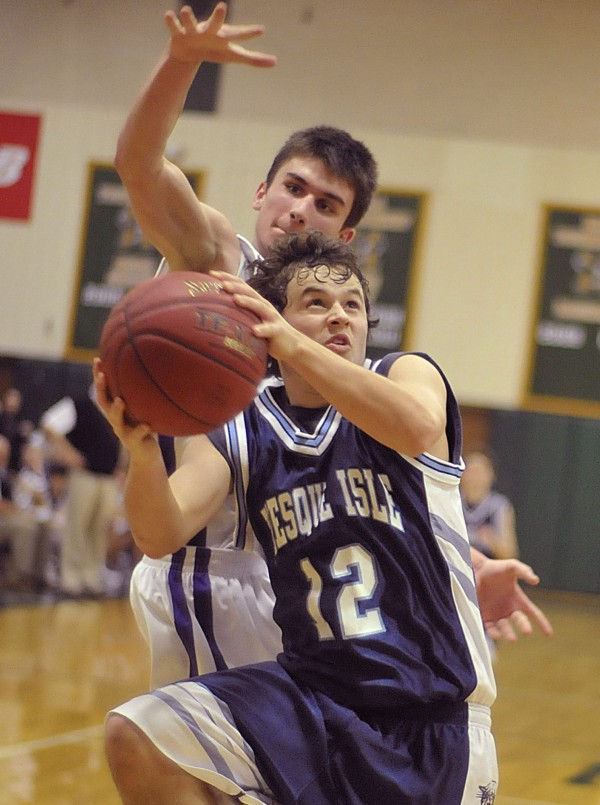 Presque Isle boys basketball player Wilder York (12) drives to the hoop after a steal with John Bapst's Colby Kohn (back) going for the block in the second half of their game at Husson' s Newman Gym Friday, Dec. 23, 2011.