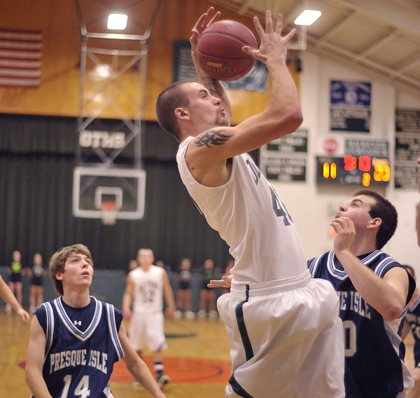 Old Town boy's basketball player Bryan Guay (40) pulls down an offensive rebound over Presque Isle players Andrew Kofstad (50) and Jonah Stephenson (14) in the first half of their game in Old Town Saturday, Dec. 17, 2011.