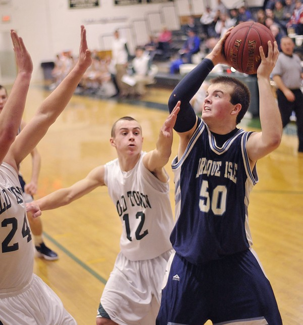 Presque Isle boy's basketball team player Andrew Kofstad (50) tries to put up a shot over Old Town player Cameron Archer (12) in the second half of their game in Old Town Saturday, Dec. 17, 2011.