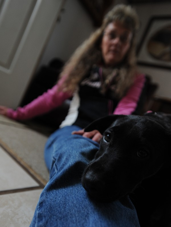 Anne Marie Messer sits with her newly adopted black lab, Bella, at her Bangor home on Wednesday, Nov. 23, 2011. Messer adopted her dog from a shelter in Georgia.