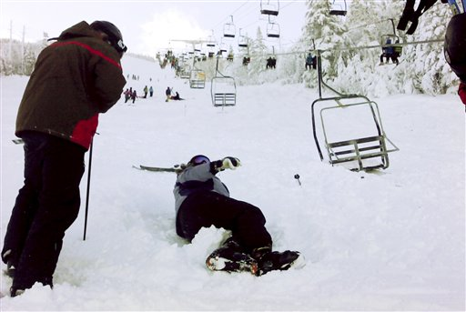 A skier comes to help a skier who fell onto the slope after a chairlift derailed at the Sugarloaf ski resort in Carrabassett Valley, Maine, on Dec. 28, 2010.