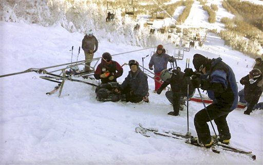 A skier who fell onto the slope after a chairlift derailed at the Sugarloaf ski resort is tended to in Carrabassett Valley, Maine, on Dec. 28, 2010.