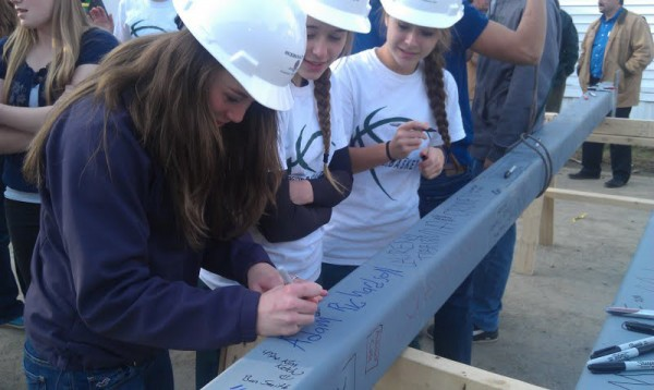 Old Town High School student Lauren Tibbits (left), 15, signs her name on one of the last two steel beams lifted onto the school's science and art expansion wing on Tuesday. Fellow students Karah Hussey (center), 14, and Rachel Martin (right), 15, watch Tibbits after signing their own names.