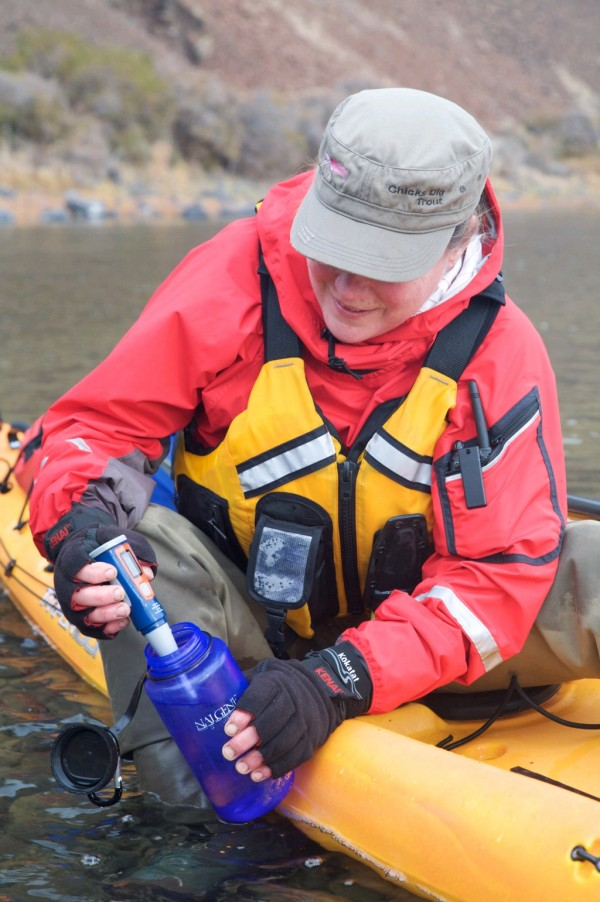 A kayaker uses the SteriPEN Journey to purify water. In about a minute, the UV technology will kill bacteria and viruses, making her water safe to drink.