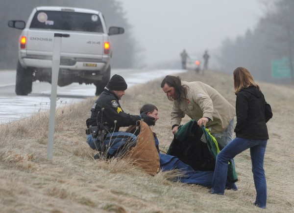 Maine State Police Sgt. Sean Hashey (left) holds the head and neck of James Haining of Newport as fellow motorist Mike Hampton of Missouri uses his jacket to provide warmth while Haining's friend Brooke McCaron watches along Interstate 95 in Hampden on Wednesday, Dec. 21, 2011. Haining''s pickup truck rolled over on the ice-covered roadway and came to rest in a swampy area off I-95. McCarron was not traveling in Haining's truck.
