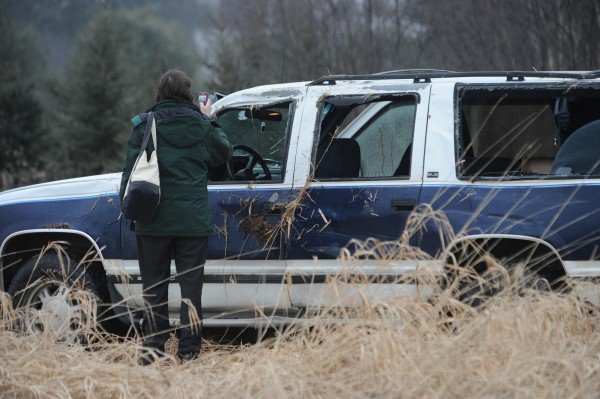 Sherry Briggs of Kenduskeag uses her cellphone to snap a picture of her SUV after she crashed it on ice-covered Route 15 in Bangor on Wednesday, Dec. 21, 2011.