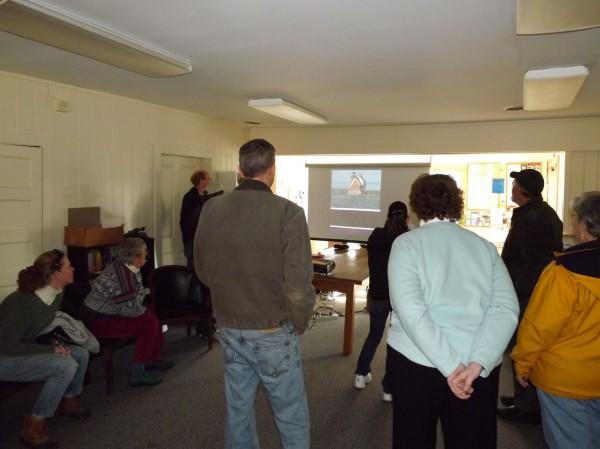 A crowd gathers inside Rockland Yacht Club to watch Gary Sredzienski of Kittery swim across Rockland Harbor via video.