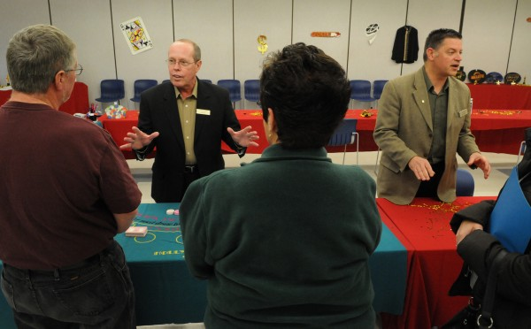 Penn National tables game expert Randy Ripple (second from left) and Hollywood Slots facility manager Michael Morris (right) offer a sales pitch to job seekers looking to fill slots as Hollywood Slots table games employees on Saturday, Dec. 17, 2011 at Eastern Maine Community College in Bangor.