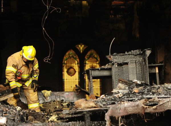 Thorndike firefighter Scott Cooper checks for what appeared to be smoulderig debris inside the Thorndile Congregational Church on Wednesday Dec. 28, 2011. The church was reported in flames by a passerby during the early morning hours of Wednesday.