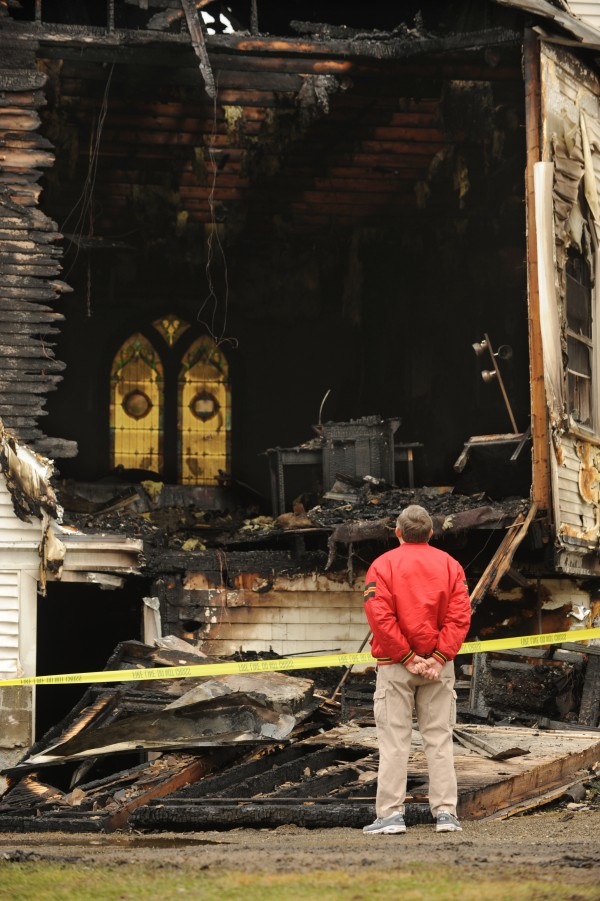 Former Thorndike Congregational Church pastor George Sadlo views the charred remains of the church he served in from 2000 to 2010 on Wednesday, Dec. 28, 2011.