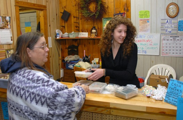 Customer Carol Clark of Millinocket talks with clerk Samantha Jones (right) as Jones rings up Clark's purchases at the Two Sisters and Friends Thrift Store on Penobscot Avenue in Millinocket on Thursday, Dec. 28, 2011.