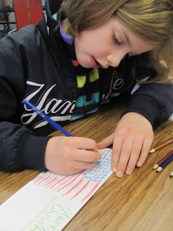 Elaine Lemieux, 8, of Topsham confirms that she has drawn all 50 stars on a drawing of the American flag she made for a soldier stationed in Afghanistan. Lemieux was one of more than 200 Woodside Elementary School students who sent letters to U.S. military personnel on Monday, Dec. 19, 2011.