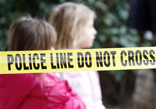 Two young girls walk by police tape that stretches through a Grapevine, Texas, apartment complex where police found seven people dead in an apartment on Sunday, Dec. 25, 2011.