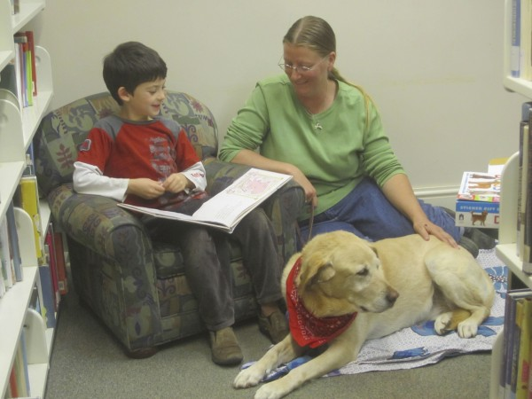 Rebecca Henderson and her &quotListening Lab,&quot Atticus, enjoy a reading session with Adam.
