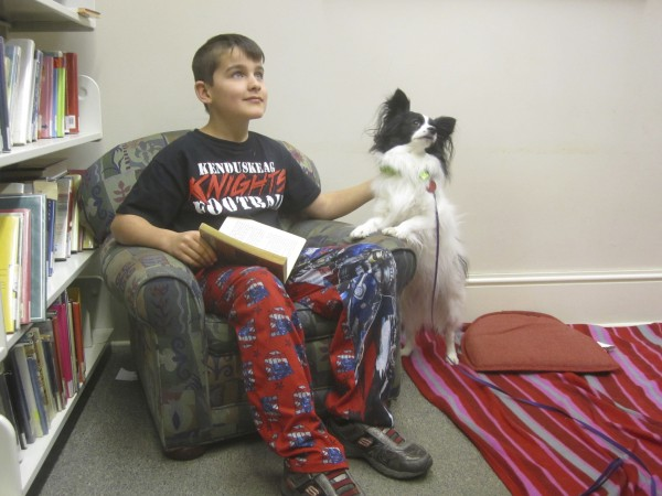 10-year-old Justin and 10-pound Finch get ready to read together.