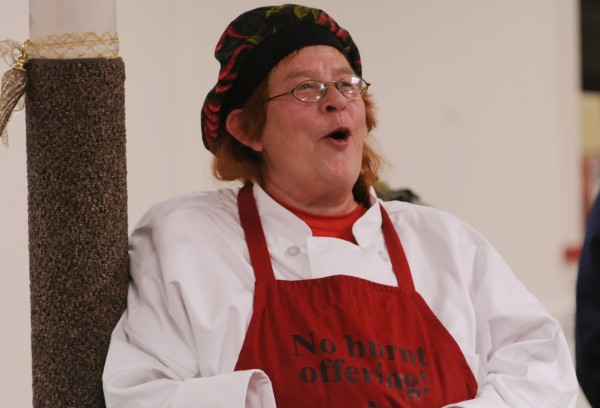 J. Faye Wolfe, head cook at the Brewer Congregational Church in Brewer leads a group of 35 people in song before they  eat a Christmas Day meal on Dec. 25, 2011, at the church.