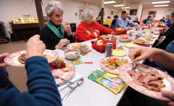 Mary Huskins (left) of Orono and Annie Dudley of Bangor share a Christmas meal at the Brewer Congregational Church on Sunday, Dec. 25, 2011.