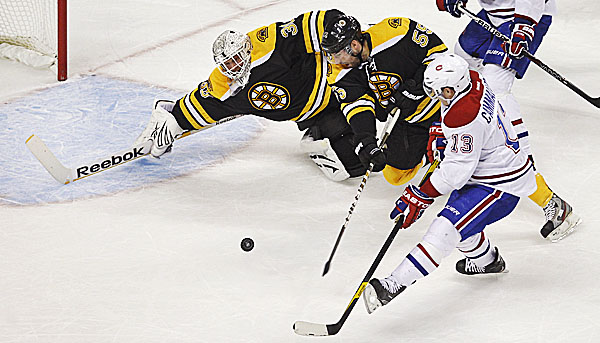 Boston Bruins goalie Tim Thomas (30) starts to dive to make a save on a shot by Montreal Canadiens left wing Mike Cammalleri (13) in the first period of an NHL game in Boston, Thursday Jan. 12, 2012. At center is Bruins defenseman Johnny Boychuk (55).