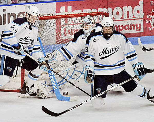 Maine defensemen Ryan Hegarty (44) and Mark Nemec (3) help goalie Martin Ouellette clear a puck during a game last season.