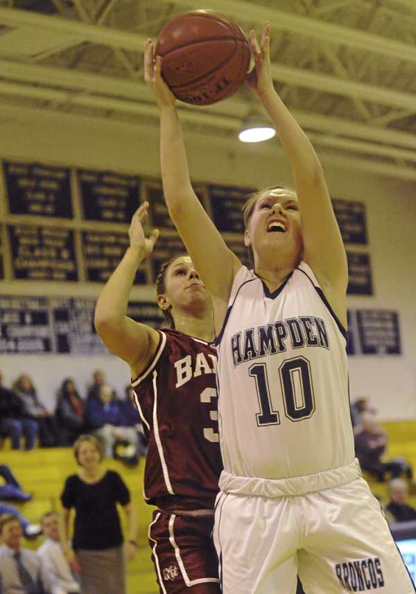 Hampden Academy's Ellie Webb (10) grabs a rebound with pressure from Bangor High School's Jordan Seekins during the third period of their game at Hampden Academy  Friday night  Jan. 20, 2012.