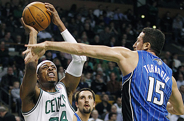 Boston Celtics small forward Paul Pierce (34) tries to shoot as Orlando Magic forward Hedo Turkoglu (15) reaches to block during the first quarter of an NBA game in Boston, Monday, Jan. 23, 2012.