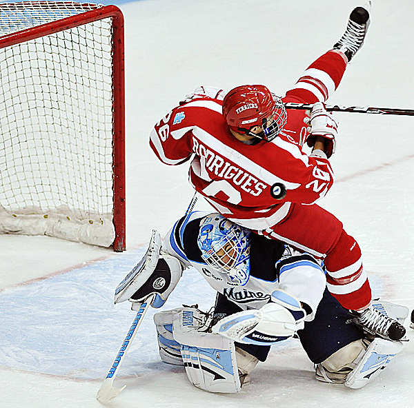 Maine goalie Dan Sullivan tries to keep his eyes on the puck as he is tackled by Boston University's Evan Rodrigues (26) in the first period of their game in Orono, Saturday Dec. 10, 2011. Maine visits BU for Hockey East games Friday and Saturday nights.