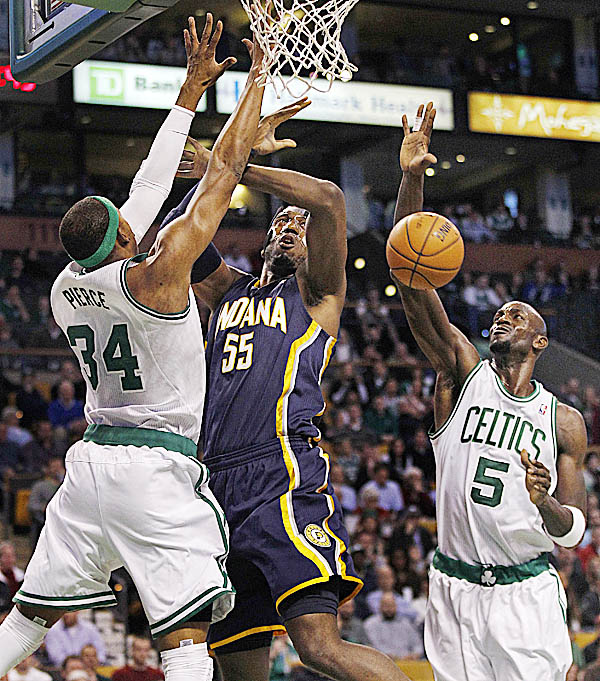 Boston Celtics' Paul Pierce (34) and teammate Kevin Garnett (5) combine to block Indiana Pacers center Roy Hibbert (55) on a drive to the basket during the first quarter of an NBA game in Boston, Friday, Jan. 27, 2012.