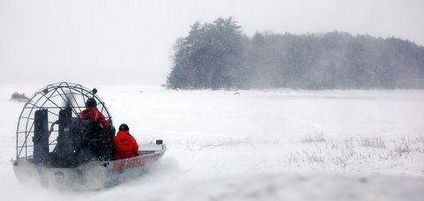 A Maine Warden Service airboat hauls divers through light snow to Eagle Island on Graham Lake on Saturday, Jan. 21, 2012 during a search of a snowmobiler who has been missing since Friday afternoon.