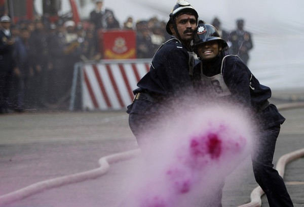 Indian firefighters aim colored water at a target during the annual fire drill competition in Mumbai, India on Monday, Jan. 9, 2012. The drill is held every year aimed at enhancing the response of the personnel to emergency situations.
