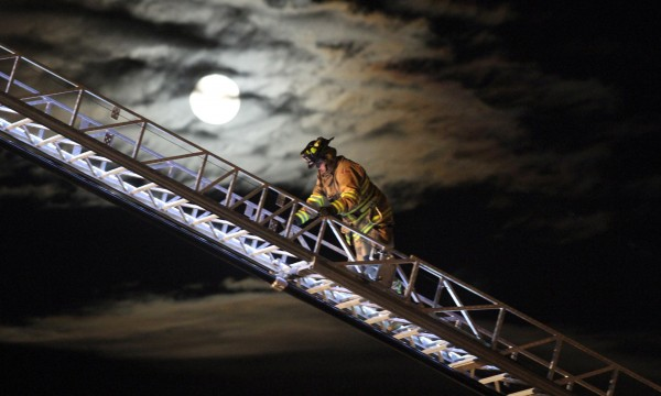 In a Sunday, Jan. 8, 2012 photo, a firefighter retreats down a ladder as the moon rises over a strip mall fire in Silverdale, Wash.