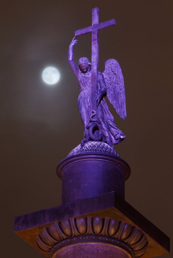 The full moon rises among the clouds behind a statue of an angel fixed atop the Alexander Column at Palace Square in St. Petersburg, Russia, late Monday, Jan. 9, 2012.
