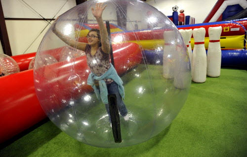 Kamryn Kiss, 15, of Glenburn, rolls across the floor in the &quothamster ball&quot to play human bowling on Wednesday, Jan. 18, 2012 at Playland Adventures on Wilson Street in Brewer.