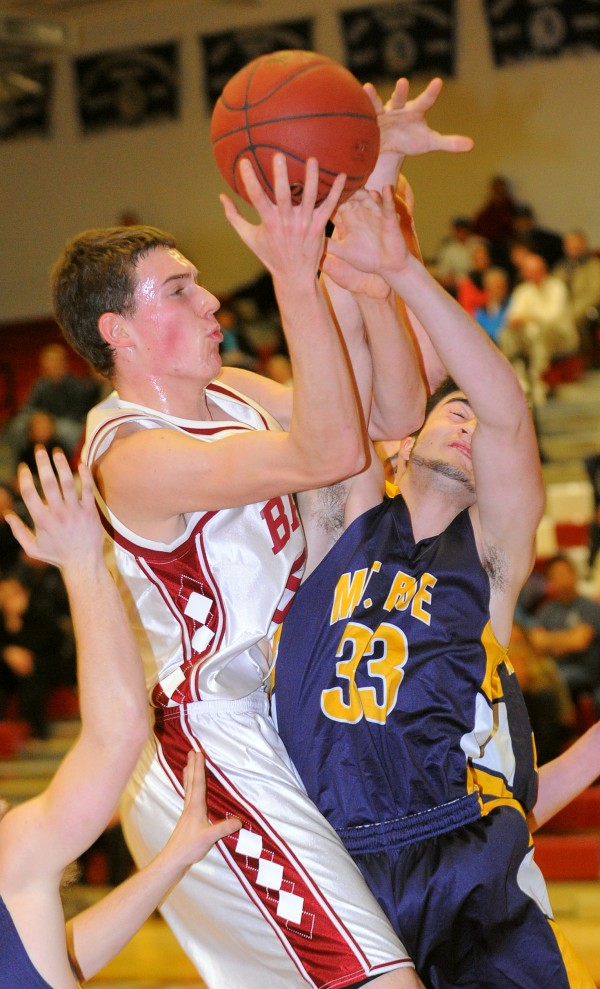 Bangor High School's Patrick Stewart (left) collides with Mt. Blue High School's Chad Luker as he drives for the basket during the first half of the game in Bangor Tuesday evening.