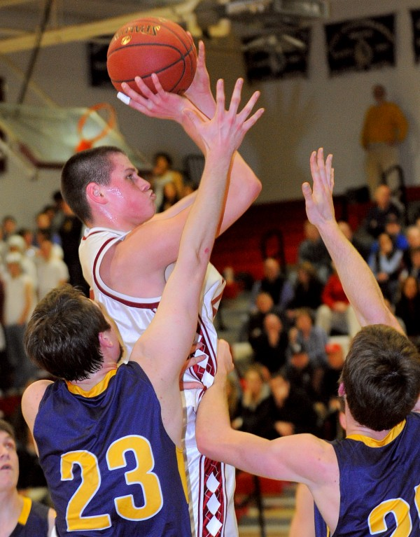 Bangor High School's Ellis Throckmorton goes up for a shot over Mt. Blue High School's Blake Hart (23) and Cam Sennick during the first half of the game in Bangor Tuesday evening.